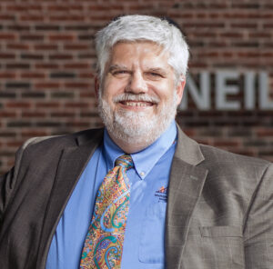"""Photo of a caucasian man with white hair and beard. He is wearing a blue shirt and colorful tie with a brown suit jacket. In the background is a brick wall with the word """"Neil"""""""