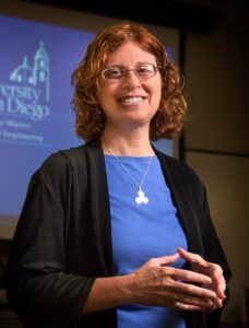 photo of smiling woman with shoulder length curly red hair. she is wearing glasses and wearing a blue top with black sweater. she is standing in front of a projected image that has math symbols