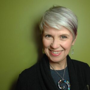 smiling white woman with gray/silver hair standing in front of a green wall. she is wearing a black sweater, a swirly shiny glass necklace and sparkly glass earrings